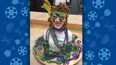 woman drapped in mardi gras beads cake